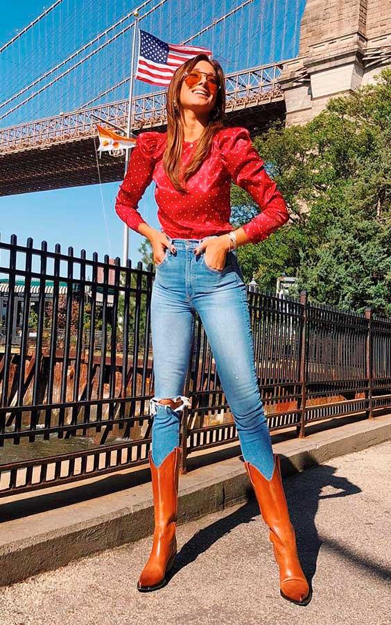 blusa de manga bufante, calça jeans e botas de cowboy