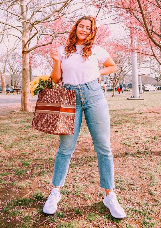 bolsa com estampa de logo, blusa branca e calça jeans