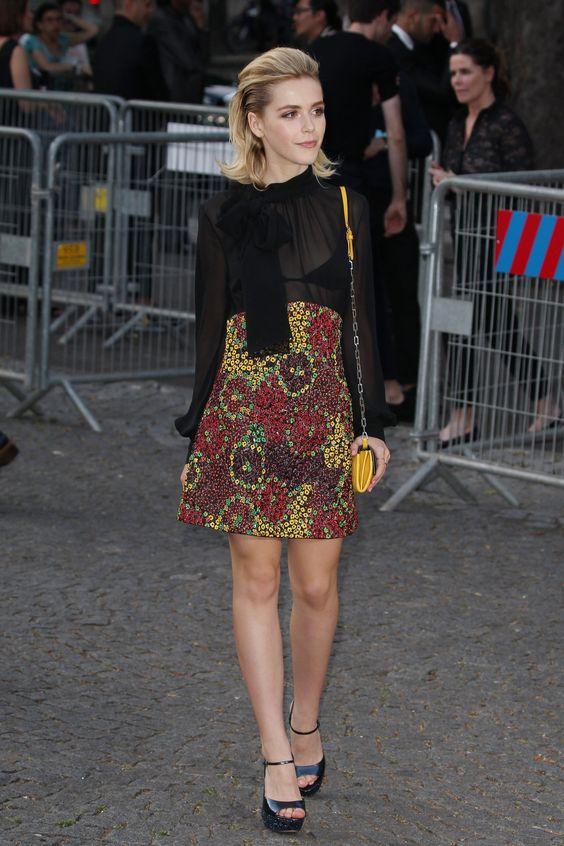 Kiernan Brennan com blusa de transparência e saia floral