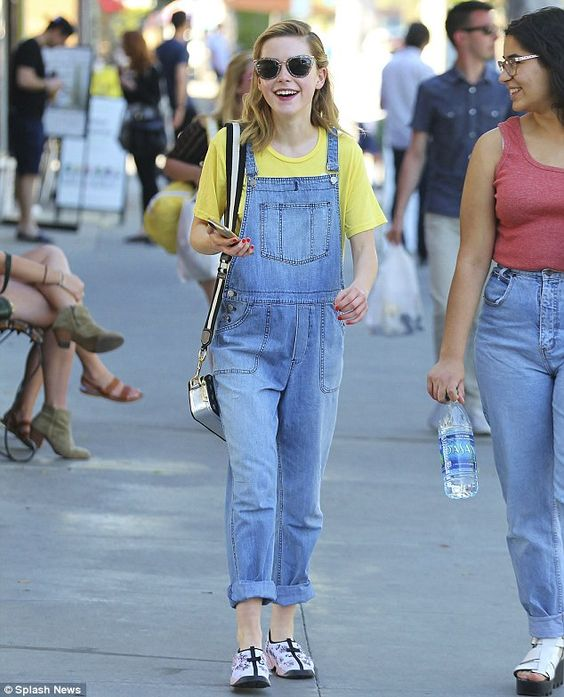 Kiernan Brennan com t-shirt amarela e jardineira jeans