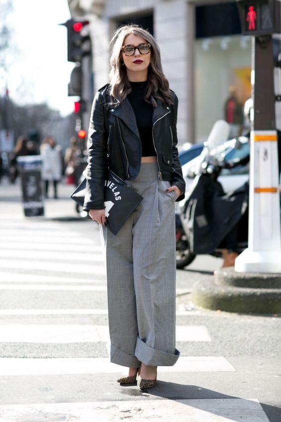 jaqueta de couro, top cropped preto de gola alta e calça de alfaiataria