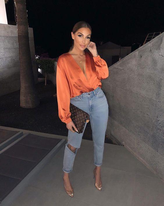 camisa laranja, calça jeans com rasgo no joelho