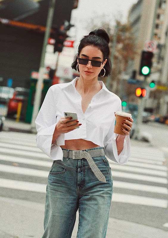 camisa branca cropped com cinto e calça jeans