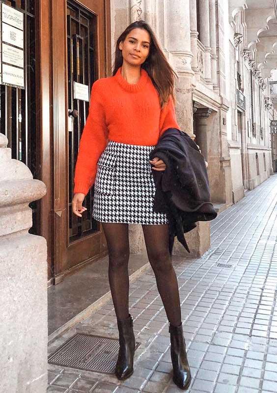 camisa laranja, minissia xadrez e meia calça preta