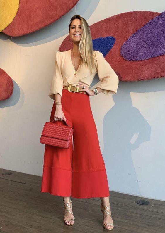 camisa em tons terrosos, calça e bolsa vermelha