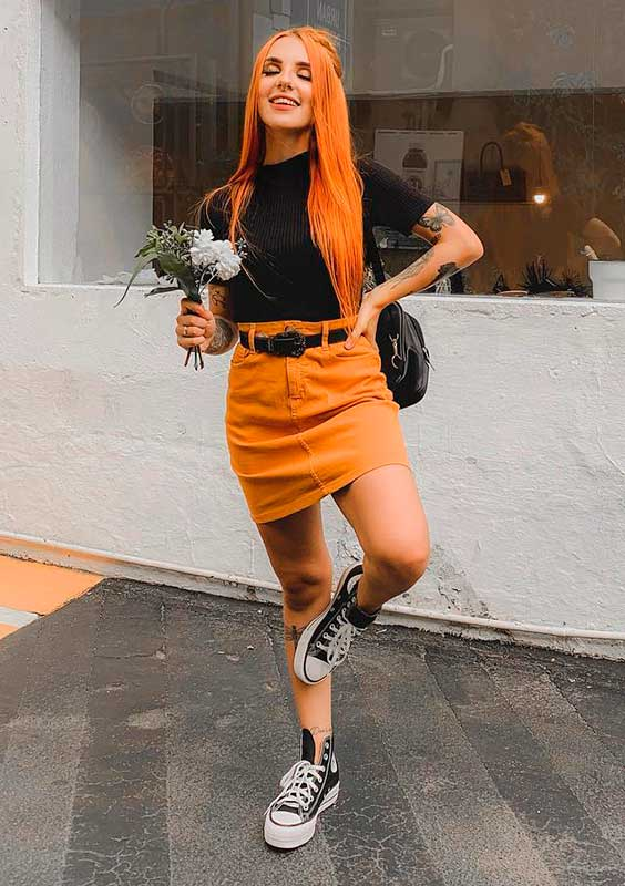 blusa preta, saia laranja e cinto preto