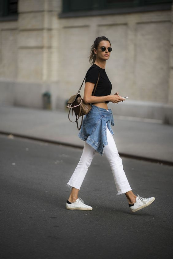 top preto e calça branca, jaqueta jeans amarrada na cintura e tênis branco