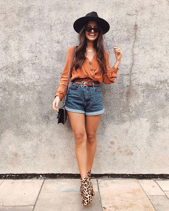 chapéu fedora, camisa terracota, shortinho com barra dobrada e botinha de oncinha