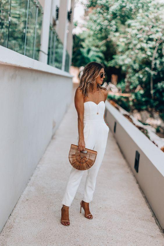 macacão branco tomara que caia, bolsa de bambu e sandália de duas tiras