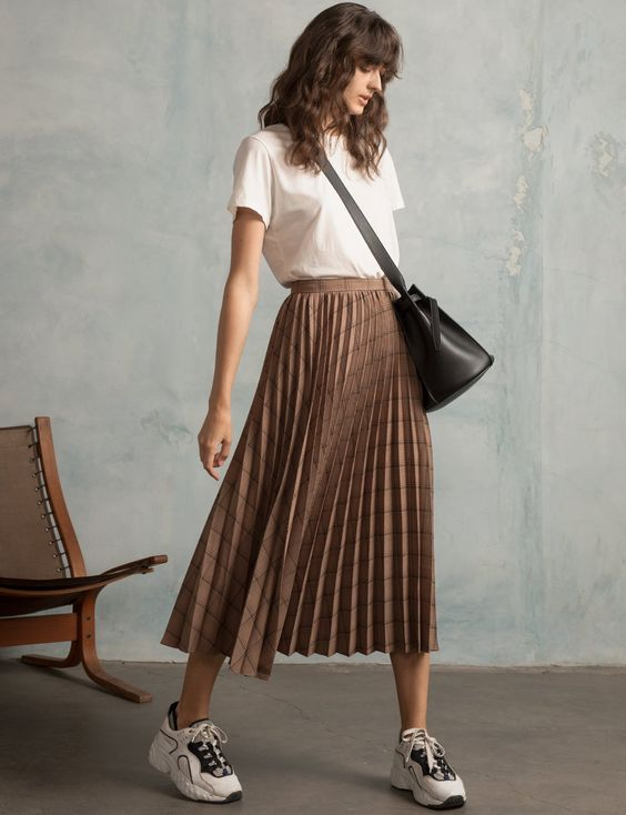 blusa branca, saia plissada marrom e tênis