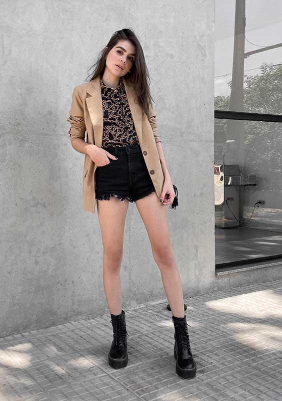 blazer bege, camisa estampada e short preto desfiado