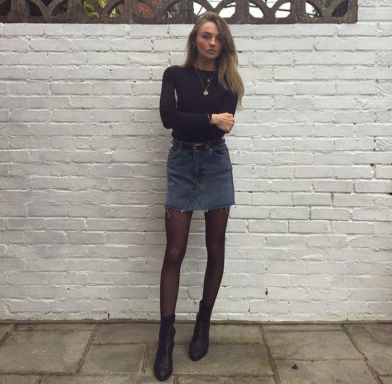 blusa preta de manga, minissaia jeans cinza, meia-calça e bota