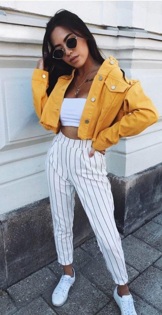 , jaqueta amarela, top faixa branco, calça listrada e tênis branco