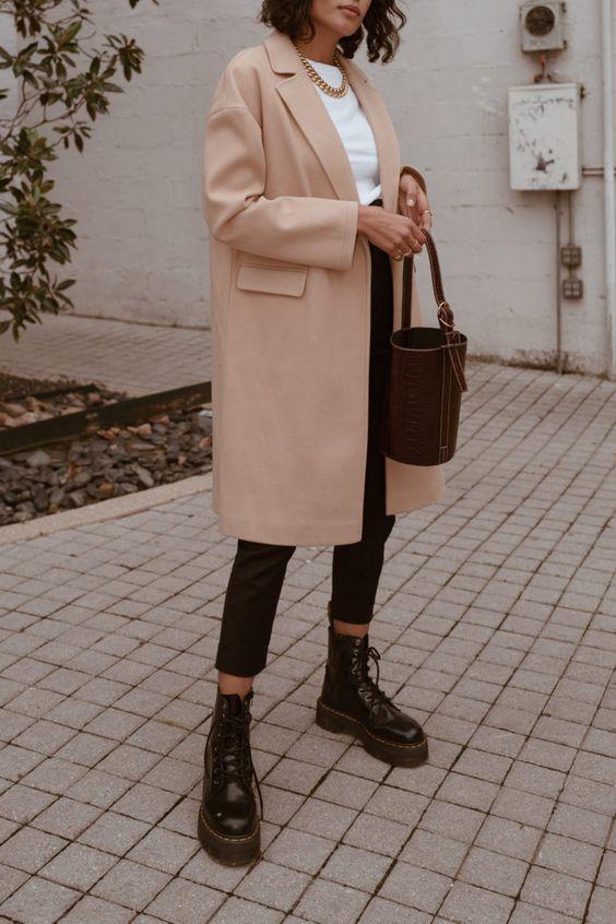 maxi casaco bege, blusa branca, calça preta e conturo Dr. Martens