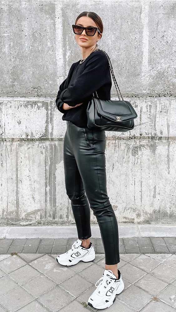 suéter preto, calça de couro e tênis branco