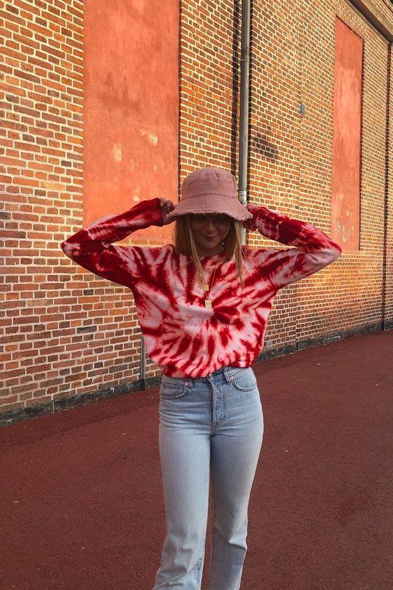 bucket hat, blusa de manga tie-dye e calça jeans