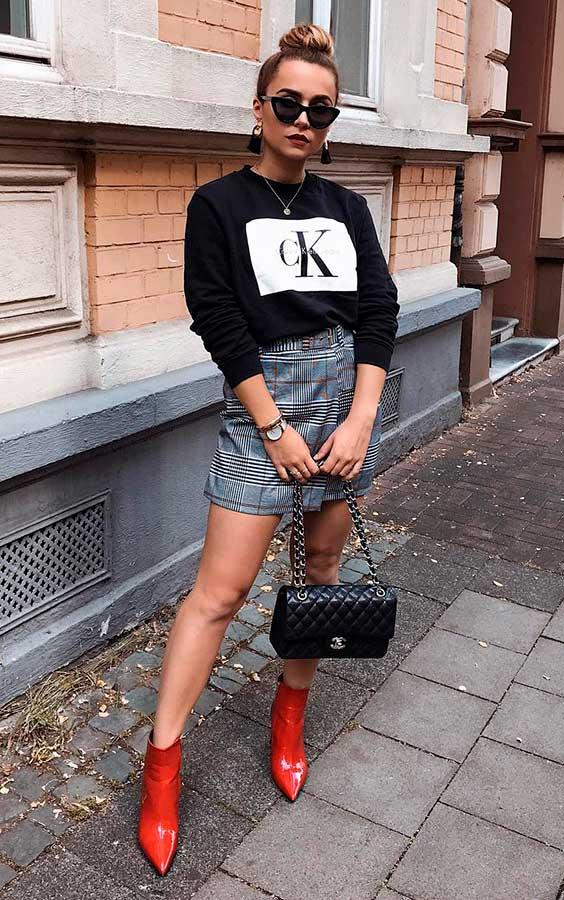 blusa de frio preta, minissaia xadrez e bota vermelha