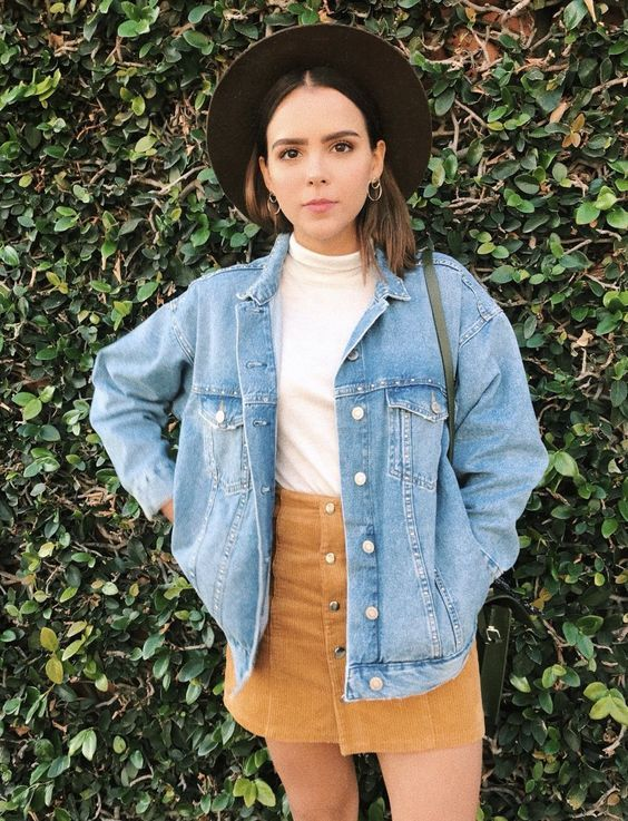 chapéu fedora, blusa branca, jaqueta jeans e minissaia de camurça