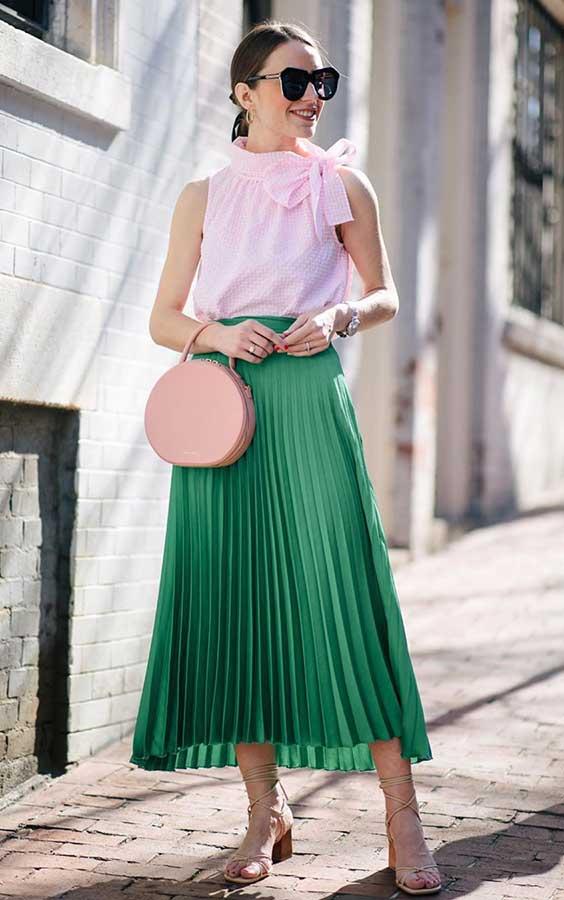 regata com laço rosa, saia midi verde plissada, sandália de tiras de bico quadrado