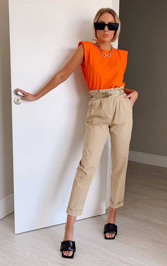 blusa laranja, calça bege, cinto dourado, tamanco de bico quadrado