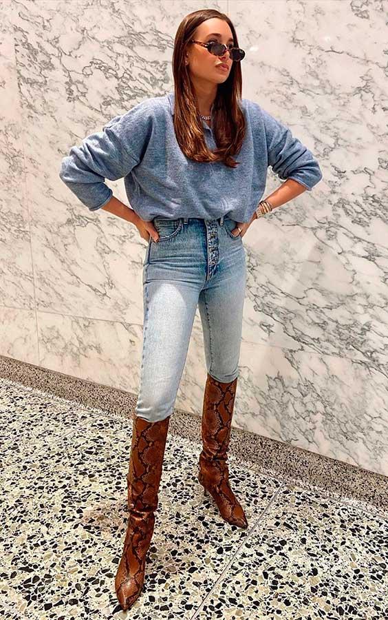 tendências de inverno, camisa azul, calça jeans e bota de cano alto
