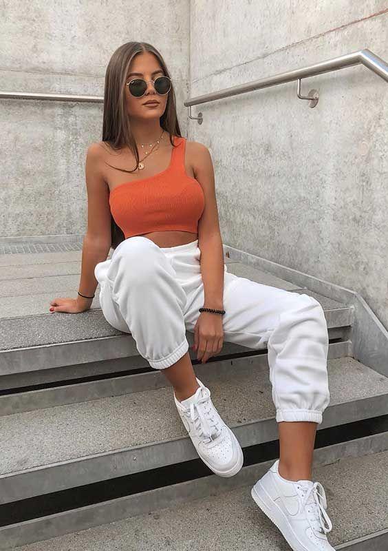 cropped laranja um ombro só, calça de moletom e tênis branco