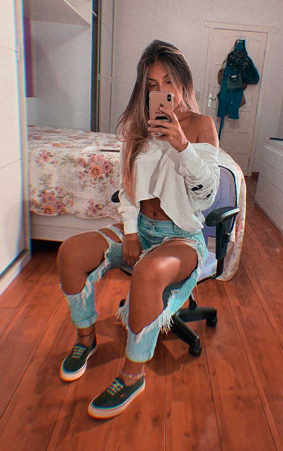 Maria Vasques, blusa de manga cropped e calça jeans destroyed
