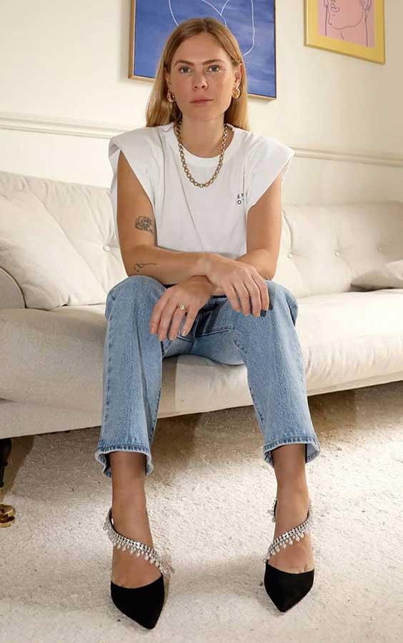 colar de corrente, mucle tee com ombreira, calça jeans e sapato de bico fino