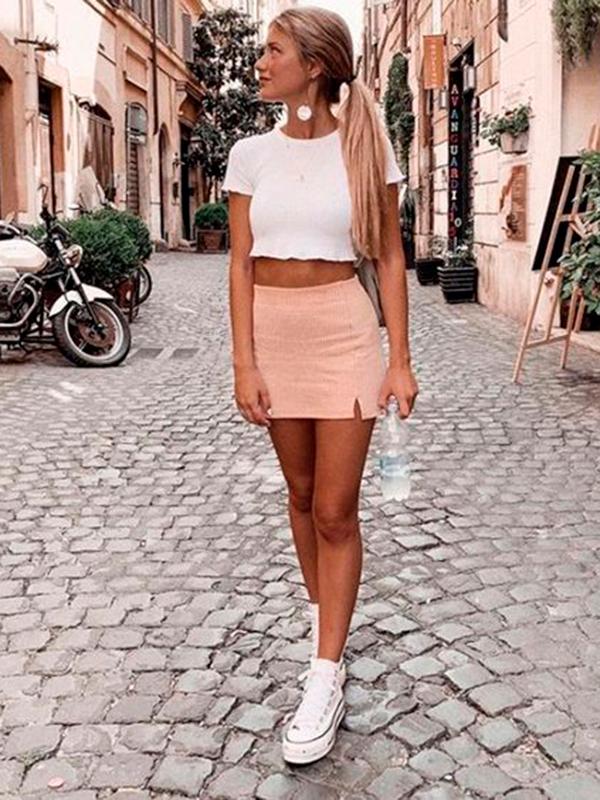 minissaia com fenda rosa, blusa branca cropped, tênis all star branco