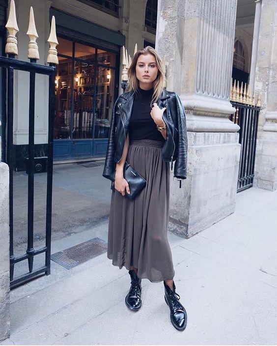 jaqueta de couro e coturno, blsua preta e saia midi