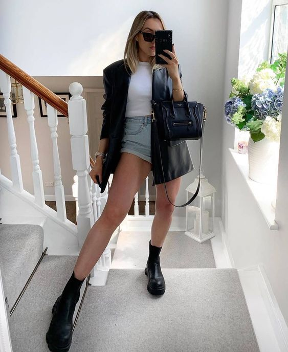 jaqueta de couro e coturno, blusa branca e short ejans