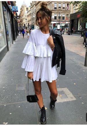 jaqueta de couro e coturno e vestido branco com babados