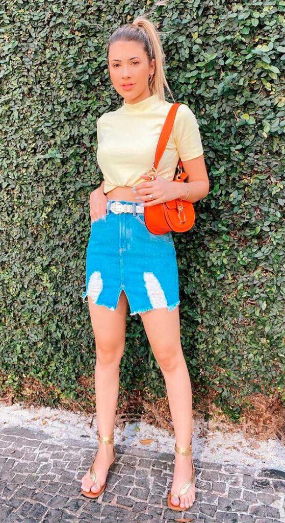 bolsa baguete vermelha, blusa de gola alta, minissia jeans, sandália de tiras douradas