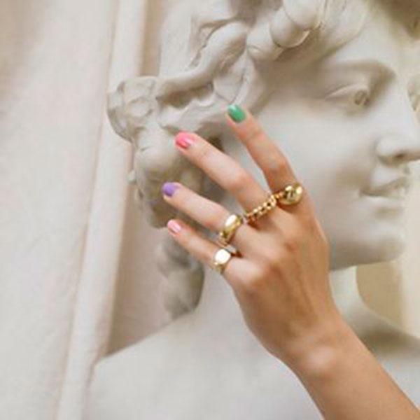unhas multicoloridas, aneis dourados