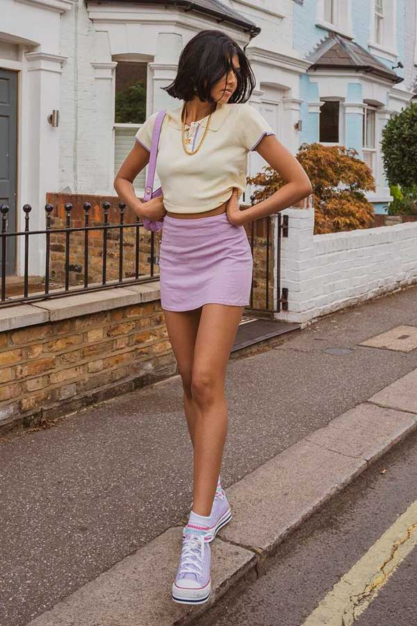 tons claros, blusa amarela e minissaia lilás