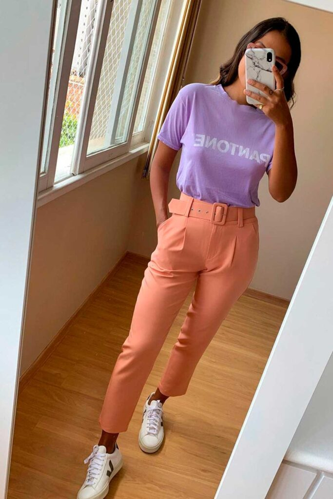 blusa lilás, calça de alfaiataria rosa e tênis branco