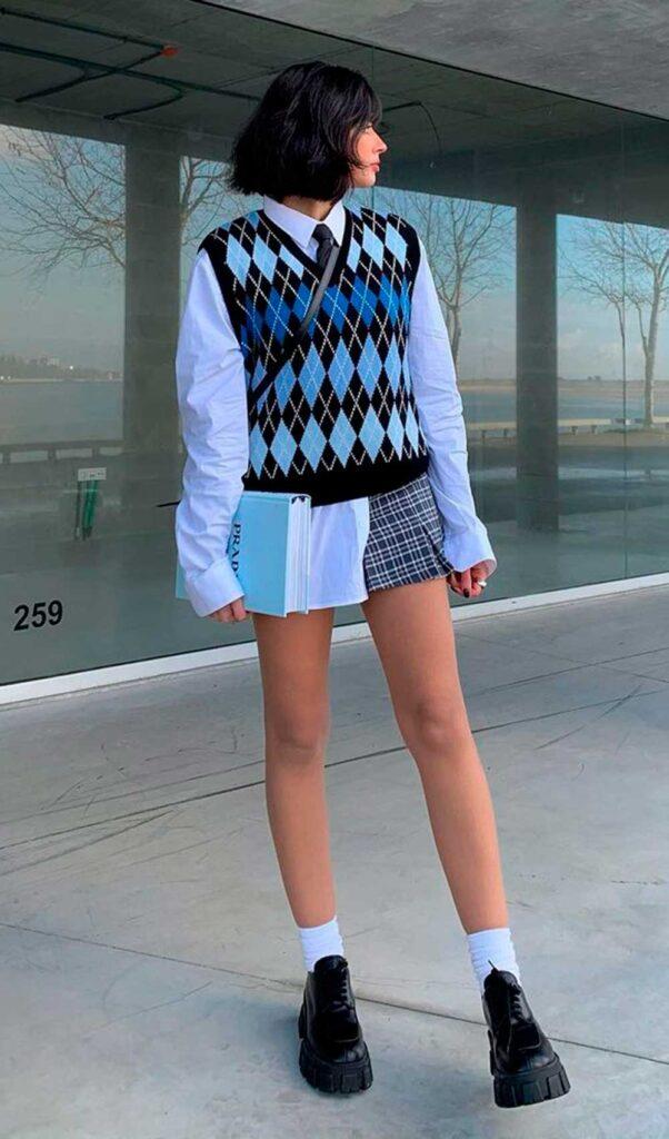 camisa branca, colete de tricô xadrez e minissaia