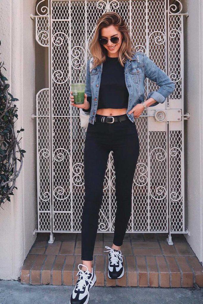 jaqueta jeans, cropped, calça preta e tênis esportivo