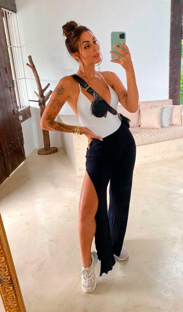 body branco, calça preta com fenda lateral e tênis esportivo