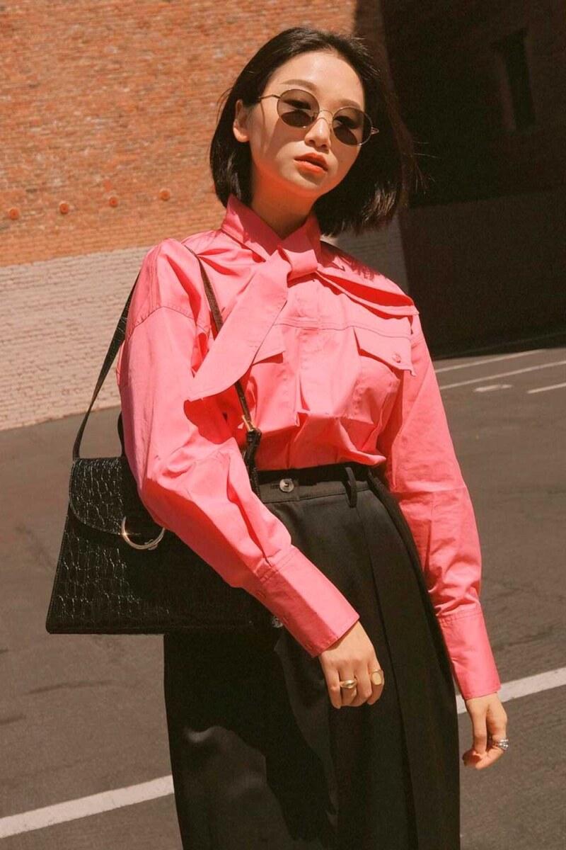 camisa rosa, bolsa baguete, e calça preta