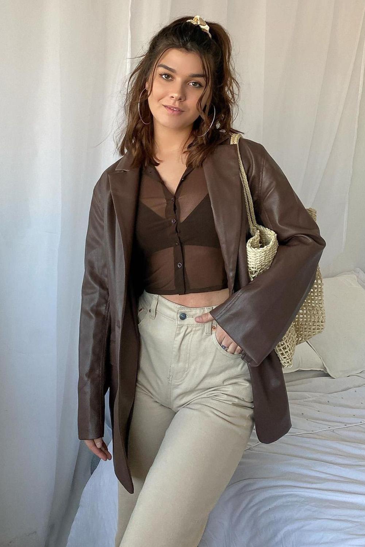 jaqueta de couro, top trasparente e calça caqui
