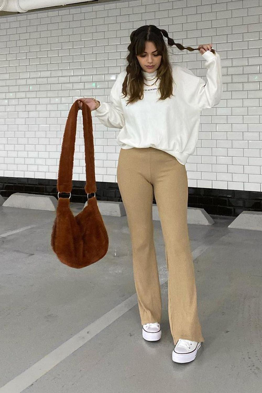 moletom branco, calça de alfaiataria bege, bolsa de pelúcioa marrom escuro