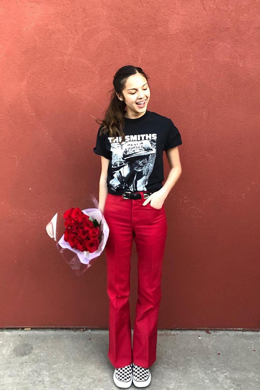 t-shirt preta, calça de alfaiataria vermelha e tênis