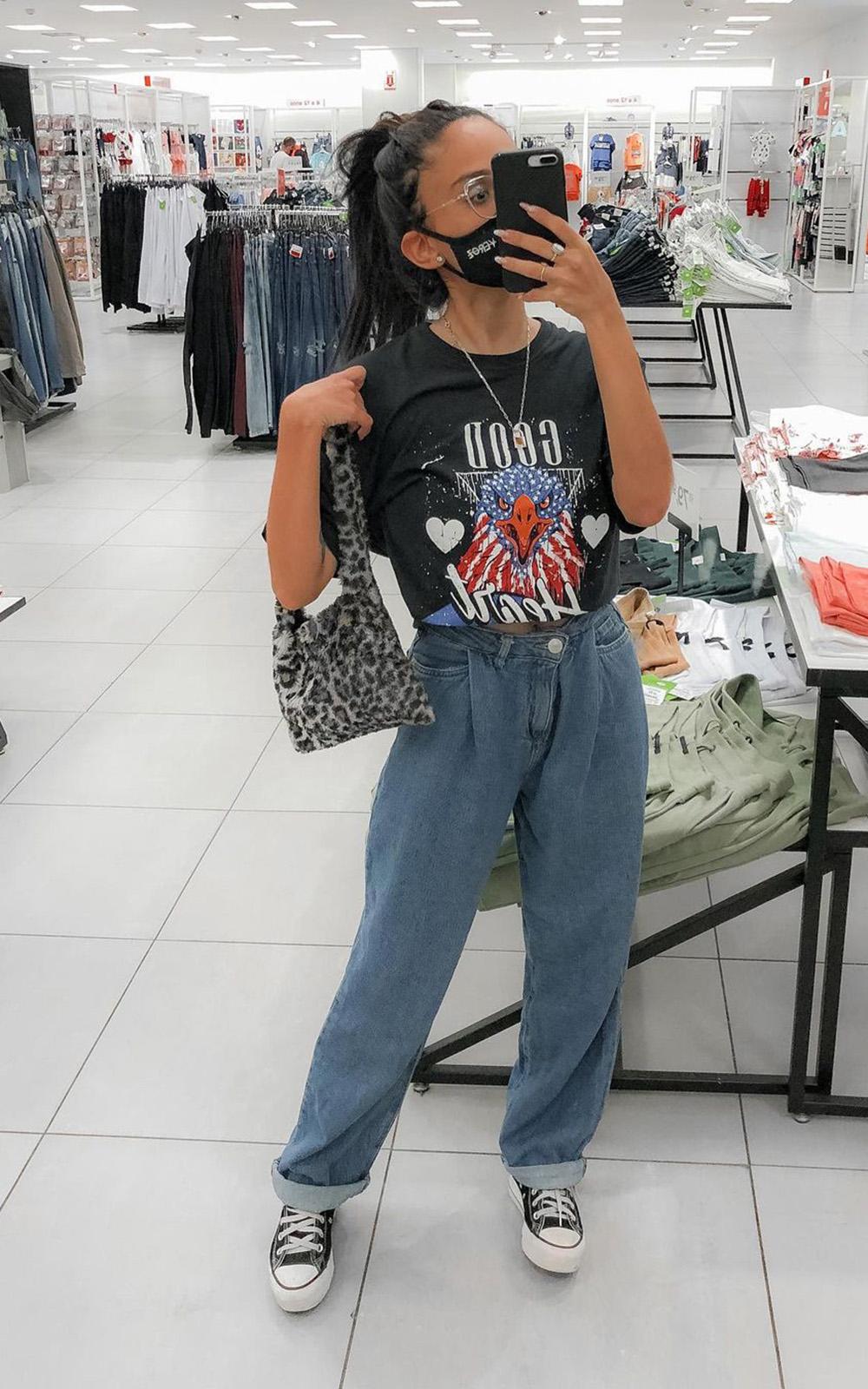 bolsa de pelúcia, t-shirt preta, calça sloucy jeans e tênis all star