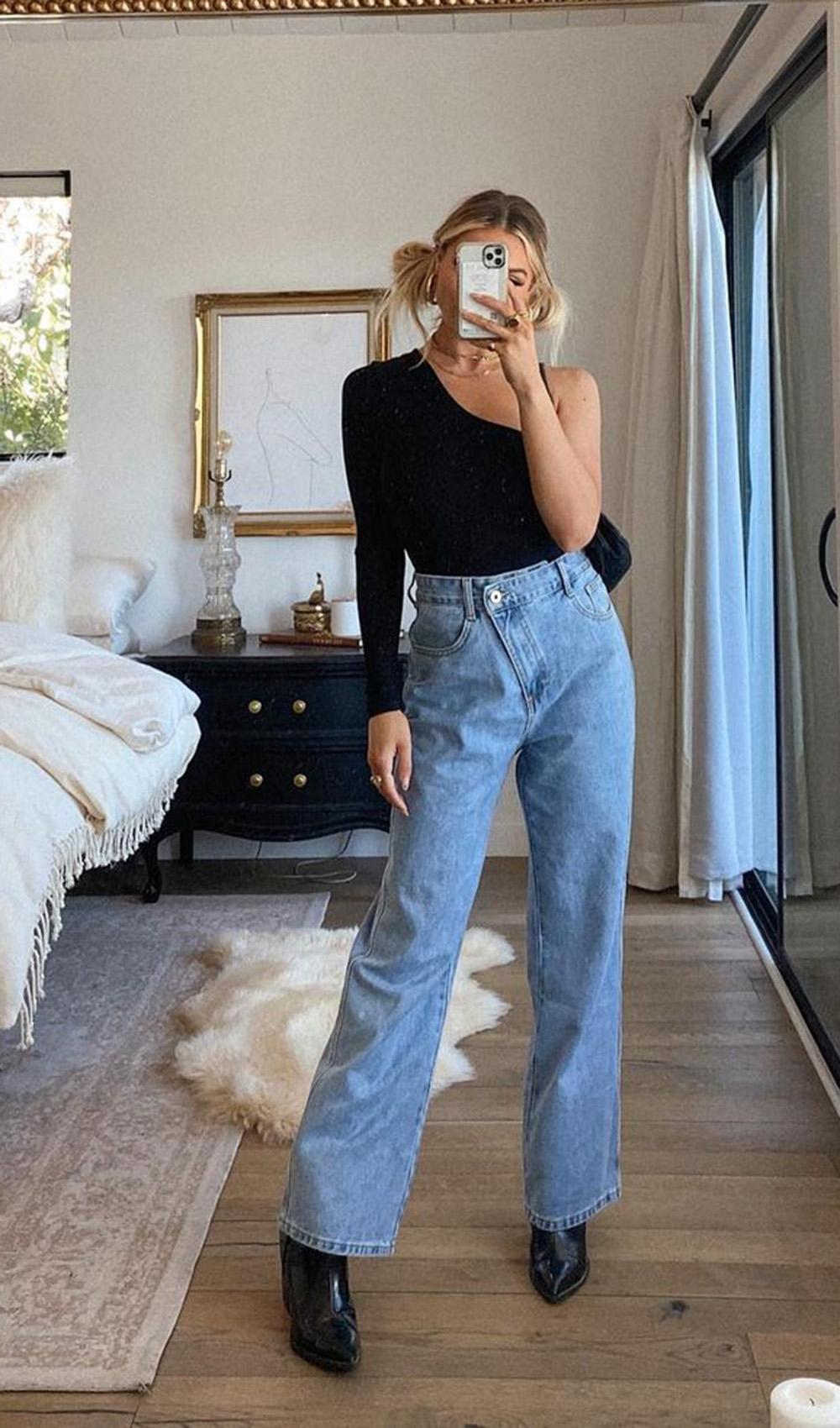 body preto com uma manga só, calça jeans e bota de bico fino