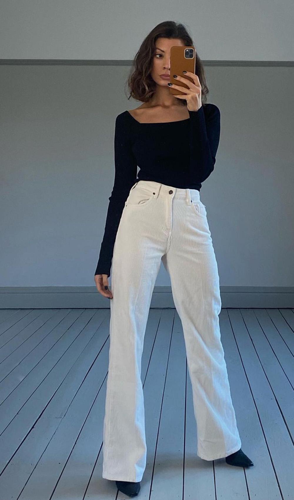 look minimalista, blusa preta. calça branca e bota de bico fino