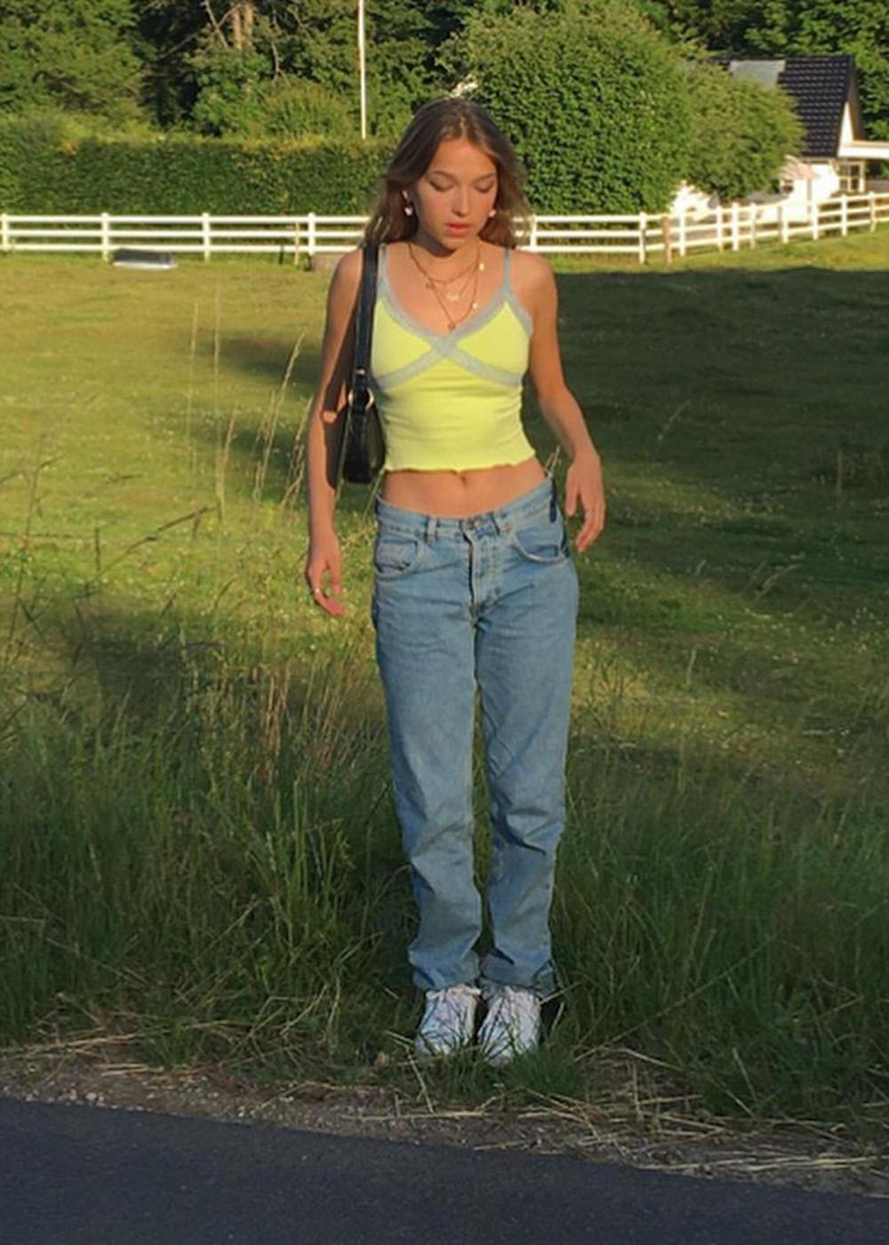 calça jeans de cintura baixa, regata amarela com renda e bolsa baguete