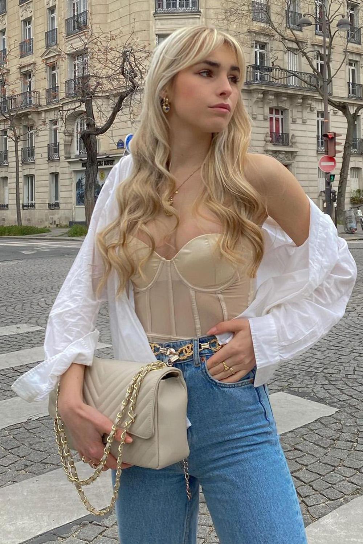 corset, camisa branca, calça jeans e cinto de corrente