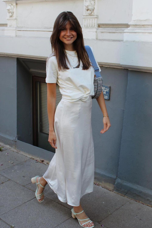 t-shirt branca, saia midi de cetim e sandália de tiras