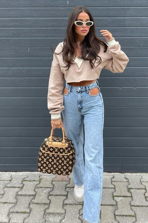 moletom cropped, jeans com recorte, bolsa de palha e tênis plataforma